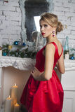 Girl in red party dress near new year tree Stock Photos