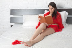 Girl in red peignoir reads a book Royalty Free Stock Images