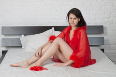 Girl in red peignoir sits on a bed Royalty Free Stock Photo