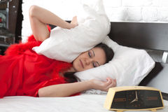 Girl in red peignoir sleeping (focus on clock) Stock Images