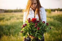 Girl with red peonies. stock image