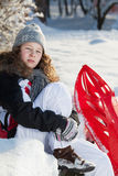 Girl with red plastic sled in a snowy park. Blond teenager girl in winter cloths sitting on a bench in a snowy park Stock Image