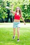 Girl in red play badminton. In park Stock Photo