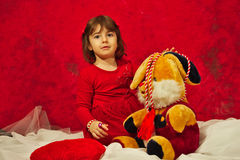 A girl in red playing with the stuffed bunny toy. A little girl dressed in red playing with a big bunny stuffed toy toy Stock Images
