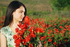 Girl on a red poppies field Stock Photography