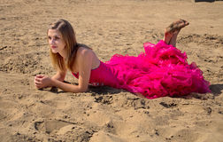 Girl in red prom dress laying on beach Royalty Free Stock Images