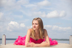 Girl red prom dress laying on boat dock Royalty Free Stock Photos