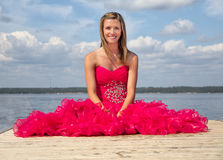Girl red prom dress sitting on dock Stock Image