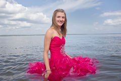 Girl in red prom dress standing in water Royalty Free Stock Photography