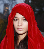 Girl in red robe. A young girl wearing a red robe or cloak as she visits Central Park in New York City. She is Portuguese and in her twenties. Image taken Stock Image