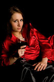 Girl red robe black satin with wine Royalty Free Stock Photos