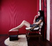 Girl in red room Stock Images