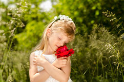 Girl with red rose. Beautiful blond little girl with flower headband holding red rose Stock Image