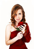 Girl with red rose. A beautiful young woman in a red dress and with long curly hair standing Royalty Free Stock Image