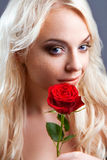 Girl with red rose in her blond hair Royalty Free Stock Photos