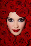 Girl in red roses Stock Photography