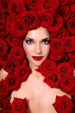 Girl in red roses Royalty Free Stock Photography