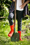 Girl in red rubber boots holding leg on shovel at garden Royalty Free Stock Photography