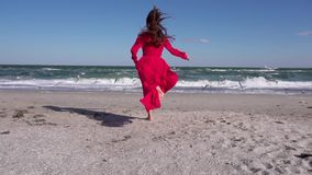 Girl in red running towards the sea slow motion stock video