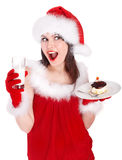 Girl in red santa hat eating cake on plate. Stock Images