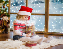 Girl in red santa hat opening gifts at Christmas Royalty Free Stock Photos