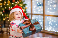 Girl in red santa hat presenting a gift Royalty Free Stock Photo