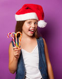 Girl in red Santas hat with candy Stock Photo