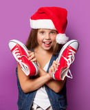 Girl in red Santas hat with gumshoes Royalty Free Stock Photo