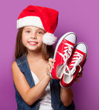 Girl in red Santas hat with gumshoes Stock Image