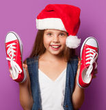 Girl in red Santas hat with gumshoes Royalty Free Stock Image
