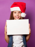 Girl in red Santas hat with white board Royalty Free Stock Images