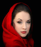 Girl in red scarf. Young woman in a red scarf on black Royalty Free Stock Photography