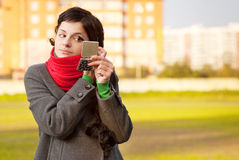 Girl with red scarf looks in mirror Stock Images