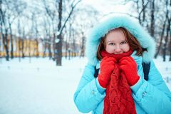 Girl in red scarf in park on a cold winter day. Smiling girl in red scarf walking in park on a cold winter day Royalty Free Stock Photography