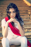 Girl with a red scarf sitting on the stairs Stock Photos