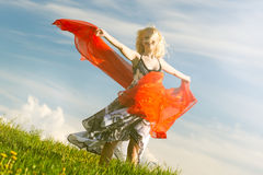 Girl with red scarf in spring, warm. Dancing girl with red scarf on meadow in spring. Warm light. Head is sharp, hands and part of cloth are slightly motion Royalty Free Stock Images