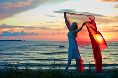 Girl with red scarf. Young woman with hands up holding red scarf in wind on the beach Stock Images
