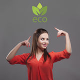 Girl in red shirt, gray background. Joyful young fashion brunette woman. Showing on eco logo Royalty Free Stock Image