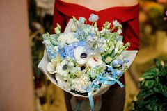 Girl holding a cute blue and white flower bouquet for the Valentine s day. Girl in a red shirt holding a cute blue and white flower bouquet for the Valentine s Stock Images