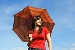 Girl in red shirt holding umbrella, blue sky Royalty Free Stock Photos
