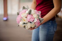 Girl holding bouquet of pink and champagne color peonies. Girl in red shirt and jeans holding in her hands bouquet of pink and champagne color tender peonies stock photography