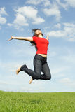 Girl in red shirt jumping on summer meadow Stock Photography