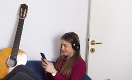 Girl in red shirt .Holds mobile and listens to music. Girl in red shirt. Listen to music on black big headphones.Next to the girl is the guitar is acoustic royalty free stock image