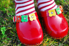 Girl in red shoes. Little girl in wooden shoes Royalty Free Stock Photos