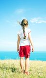 Girl in red shorts. Looks into the sea on a bright sunny day Stock Image