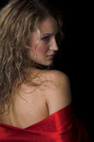 Girl in red silk. Young woman in red silk isolated in the black background stock photography
