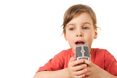 Girl in red sing in old style microphone. Pretty little girl in red sing in old style microphone isolated on white background Stock Photo
