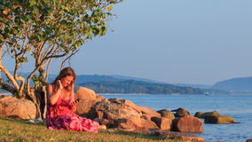 Girl in Red Sits on Beach Checks Iphone at Sunset by Rocks. Blond girl in red frock sits on grass beach under tree near rocks checks iphone against sea hills at stock video