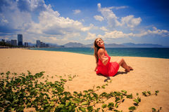 Girl in red sits on sand looks at sea on foreground creepers Royalty Free Stock Image