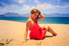 Girl in red sits on sand touches hair looks downward against sea Stock Photo